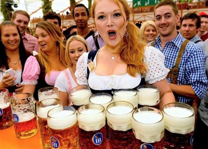 Una kellerina trasporta numerosi boccali di birra